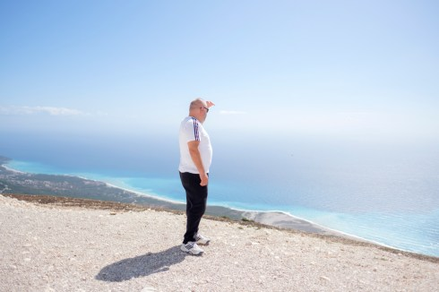 """Artan Hoxha, a 43-year-old Albanian investigative journalist for the """"24 News"""" TV, looking at the coast of Sarandë, where he affirms that the majority of drug cartels' properties are to be found, including those of fugitive criminal Klement Balili. Llogara, Albania 2017. © Matteo Bastianelli"""