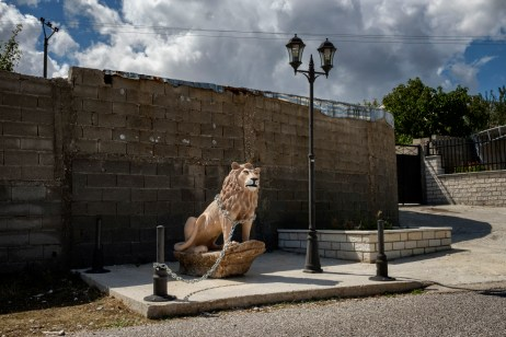 The statue of a lion chained to a pole in the vicinity of a villa in Lazarat. The village was known as the European capital of cannabis until 2014, when a major raid carried out by the Albanian government destroyed the local production and trafficking. Lazarat, Albania 2017. © Matteo Bastianelli