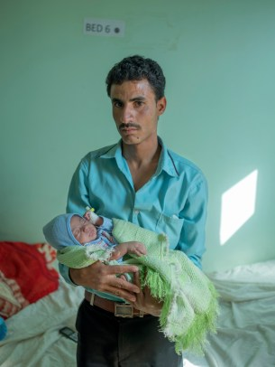 """A father holds his baby at the Mother and Child Hospital after the child was treated for a respiratory infection. Doctors and nurses have fled Yemen, leaving hospitals stretched thin. """"A lot of my colleagues have already left or are trying to travel to the Gulf states to find a better life,"""" says one Yemeni doctor working in Sanaa. Taiz, Yemen 2018. © Matteo Bastianelli"""