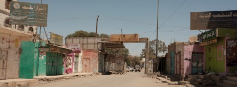 The gates of the Al-Nasser Hospital (in the center), where a notice regarding the ban on introducing knifes, bombs and weapons is hung outside. On the right, some goats are seen sleeping in front of the shops and the stands during the Friday pray. Ad Dhale, Yemen 2018. © Matteo Bastianelli