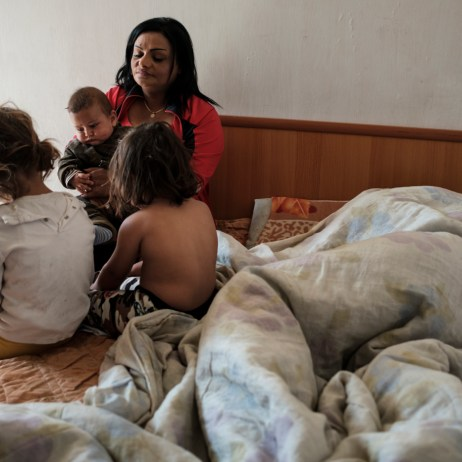 40-year-old Orkida Driza is seen with her three grandchildren Vjollca (5 yrs old), Sabina (3 yrs old) and Rexhepi (3 months old) on the bed of her 19-year-old daughter Bleona, who is resting under the covers next to them. Orkida was given in marriage at the tender age of 14 by her family, her daughter Bleona got married at 12 years old. Tirana, Albania 2019. © Matteo Bastianelli