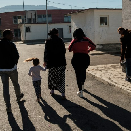"40-year-old Orkida Driza is seen walking along with other members of the Romani community living in the settlement. Orkida was given in marriage at the tender age of 14 by her family, she's divorced now and has five children. She is currently the leader of the Roman Organization ""Catia e Gruas Rome"", which stands for the rights of the Roma minorities in Tirana, Albania 2019. © Matteo Bastianelli"