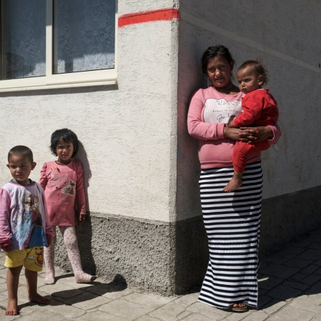 18-year-old Xhensila Bukri portrayed in front of her apartment with her 2-month-old son Arben Bukri on her lap and her daughters Megi (2 yrs old) and Pamela (3 yrs old) standing next to her. Xhensila was given in marriage at the tender age of 12, her husband is currently in prison. Tirana, Albania 2019. © Matteo Bastianelli