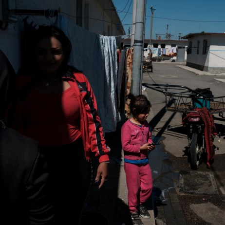 "40-year-old Orkida Driza is seen talking with other members of the Romani community living in the settlement, while some kids play around a motorcycle cart . Orkida was given in marriage at the tender age of 14 by her family, she's divorced now and has five children. She is currently the leader of the Roman Organization ""Catia e Gruas Rome"", which stands for the rights of the Roma minorities in Tirana, Albania 2019. © Matteo Bastianelli"