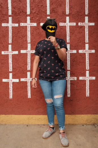 """27-year-old Jeimy Elisuath Hernández, who came from Peñablanca Cortés, Honduras, is seen portrayed while hiding her face with her Batman's hat. Behind her, a wall painted with crosses reporting the names of migrants who found shelter in """"Casa del Buen Samaritano"""" and, after starting their journey to the US border, they disappeared. Jeimy left Honduras on February 2019 due to the presence of gangs near her home and covered her face for fear of repercussions. She hopes to get to the USA in order to have a peaceful life. Oaxaca de Juarez, Mexico 2019. © Matteo Bastianelli"""