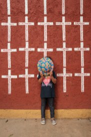 "A 4-year-old girl, who came from Honduras along with her parents in order to reach the USA, is seen portrayed while hiding her face with a hat. Behind her, a wall painted with crosses reporting the names of migrants who found shelter in ""Casa del Buen Samaritano"" and, after starting their journey to the US border, they disappeared. Oaxaca de Juarez, Mexico 2019. © Matteo Bastianelli"