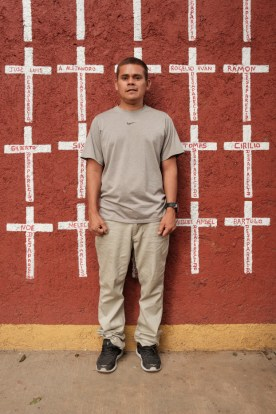 """34-year-old Edwin Noel Mejía Nolasco, who came from Honduras, is seen portrayed at the shelter of """"Casa del Buen Samaritano"""". Behind him, a wall painted with crosses reporting the names of migrants who found shelter there and, after starting their journey to the US border, they disappeared. Nevertheless, Edwin hopes to reach his relatives in South Carolina. Oaxaca de Juarez, Mexico 2019. © Matteo Bastianelli"""