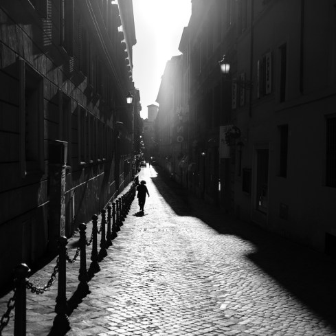 """A woman walks through an alleyway in the city centre on the day that the World Health Organization (WHO)declaredthe Coronavirus outbreak apandemic. Following the dispositions of the Prime Ministerial Decree """"I stay home"""", people shouldstay home except forwork needs, situations of necessity and health reasons. Rome, Italy 2020. © Matteo Bastianelli"""