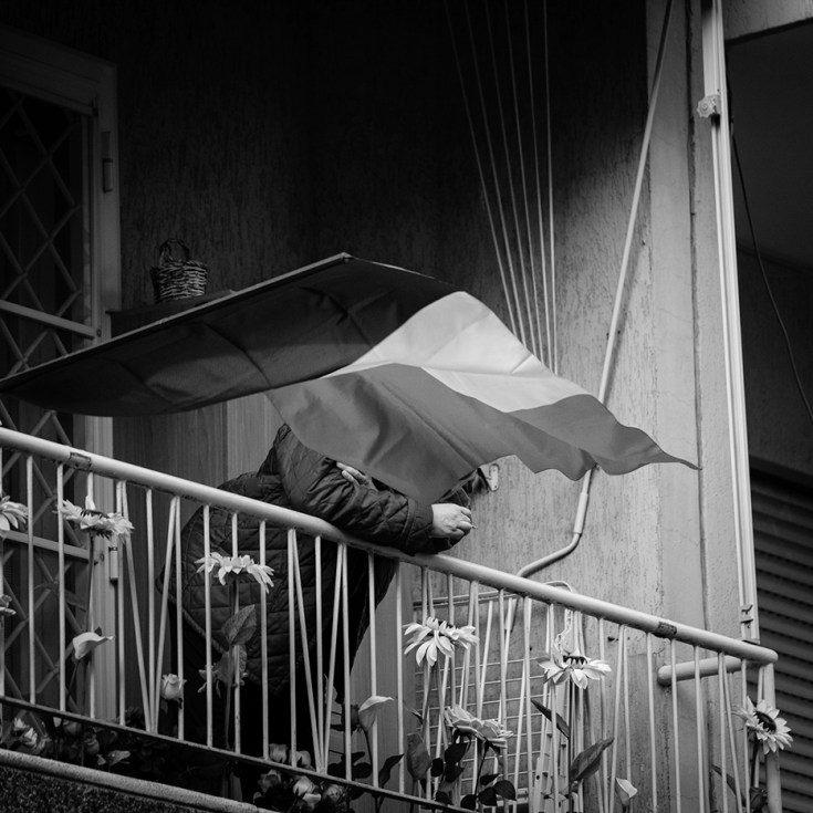 A man is seen on his balcony, covered behind an Italian flag. Italy remains locked down to help contain the spread of coronavirus. Rome, Italy 2020. © Matteo Bastianelli