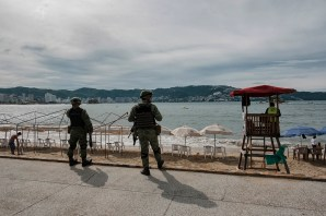Two members of the Mexican Army are seen patrolling the Hornos beach in Acapulco. One of the oldest beach resorts in Mexico, once known as a holiday destination for Hollywood stars and millionaires, Acapulco has recently been ranked as the second most violent city in the world in 2018 with a rising number of extortions, kidnappings, and murders. Acapulco, Mexico 2019. © Matteo Bastianelli