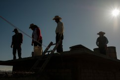 Patricia Eduviges Silva López, school teacher and leader of a local NGO, is seen on the roof of a small building with some people of the Mogote Colorado village, working on the construction of a rainwater harvesting tank to collect and treat water for domestic and agricultural use. Santiago Ayuquililla, Mexico 2019. © Matteo Bastianelli