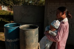 A young woman with a child in her arms, is seen walking near a rainwater harvesting tank under construction in the village of Mogote Colorado. The access to clean water for domestic and agricultural use is a daily issue in rural ares throughout southern Mexico. Santiago Ayuquililla, Mexico 2019. © Matteo Bastianelli