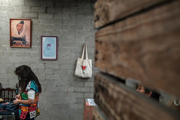 """38-year-old Reyna Ramírez Sánchez, founder and activist of the """"Obreras Insumisas"""" collective, is seen sewing bags in the kitchen while her mother looks at her. Although Reyna started sewing at a young age, she had to stop working in the maquilas after having been threatened and suffered violence for defending workers' rights with her collective. Tehuacán, Mexico 2019. © Matteo Bastianelli"""