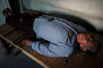 A man is seen laying on a wooden cot, undergoing a magnetic therapy session carried out by local traditional healers. Santa Cruz Loma Lapa, Mexico 2019. © Matteo Bastianelli