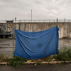 A tarp hung to dry on a fence in the vicinity of the Roma Tiburtina railway station. Hundreds of migrants are forced to live on the streets without any institutional support during Italy's lockdown aimed at stopping the spread of coronavirus. Only a few associations and NGOs are taking care of them, giving information about the Covid-19 virus and the importance of social distancing, and providing them with masks, hand sanitizer, self-certifications, food and blankets. Rome, Italy, April 2020. © Matteo Bastianelli/National Geographic Society Covid-19 Emergency Fund