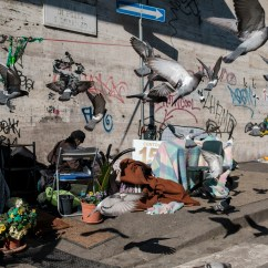 Some pigeons fly over the makeshift shelter of a Moroccan homeless living in the vicinity of the Termini station. Around 8 thousands vulnerable people are forced to live in the streets in Rome, even during Italy's lockdown aimed at stopping the spread of coronavirus. Rome, Italy, April 2020. © Matteo Bastianelli/National Geographic Society Covid-19 Emergency Fund