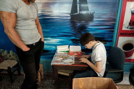 39-year-old Ibrahim Shehabi looks at a boy preparing cigarettes to sell on the street. Istanbul, Turkey 2016. © Matteo Bastianelli