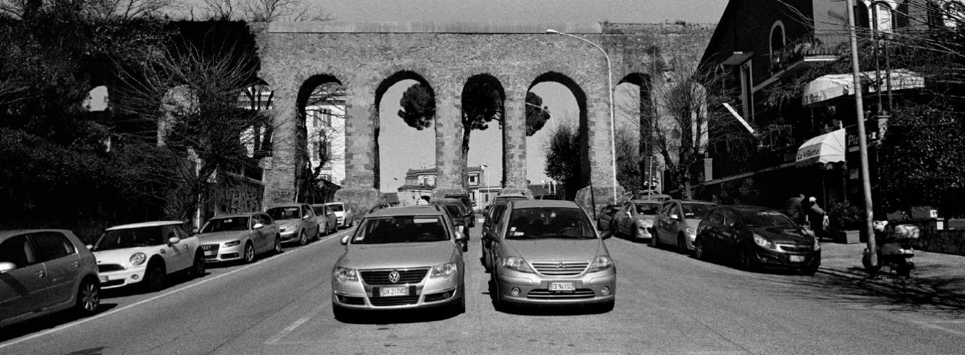 A view of the remains of the ancient Roman aqueduct surrounded by parked cars in the Pigneto neighborhood. Rome, Italy 2015. © Matteo Bastianelli