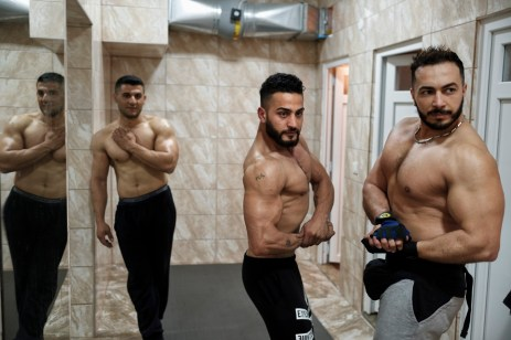 39-year-old Syrian bodybuilder, Ibrahim Shehabi, monitors the poses performed by his friends Hassan, 28, and Omar, 29. Ibrahim trains with them to compete in international bodybuilding contests. Istanbul, Turkey 2016. © Matteo Bastianelli