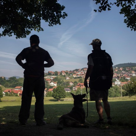 Two dog trainers rest in the shadow with a Belgian Shepherd dog while, on the background, a soldier is training a dog for mine detection purposes. Vogošća, Bosnia and Herzegovina, 2014.