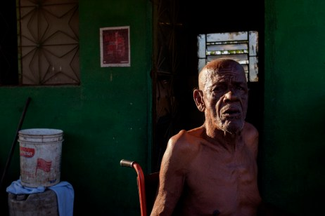 A man sits in front of his house in the former dump of Jardim Gramacho, closed in 2012 after being in operation for 34 years and then turned into a favela. Favela inhabitants received 14 thousand Reais in severance pay but they have been left without work despite the promise of reintegration. Rio de Janeiro, Brazil 2015. © Matteo Bastianelli