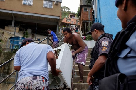 Two guys are seen moving a washing machine down the stairs of the favela of Cantagalo while two UPP policemen (Pacifying Police Unit) look on. Rio de Janeiro, Brazil 2015. © Matteo Bastianelli