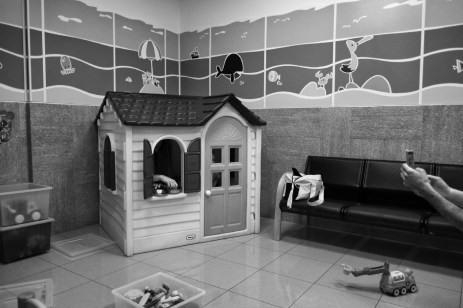 3-year-old Alen Smajic, in the play area of the Italian Ocular Centre, while his father Adis takes his picture. Rome, Italy 2016. © Matteo Bastianelli