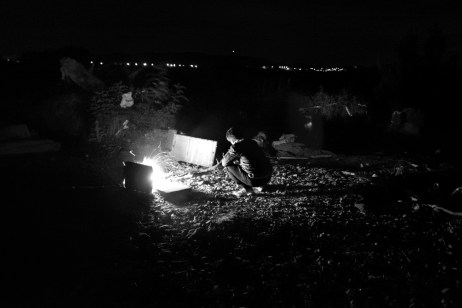 A refugee lights a fire to warm himself during a cold night in the buffer zone between FYROM and Greece. Idomeni, Greece 2015. © Matteo Bastianelli