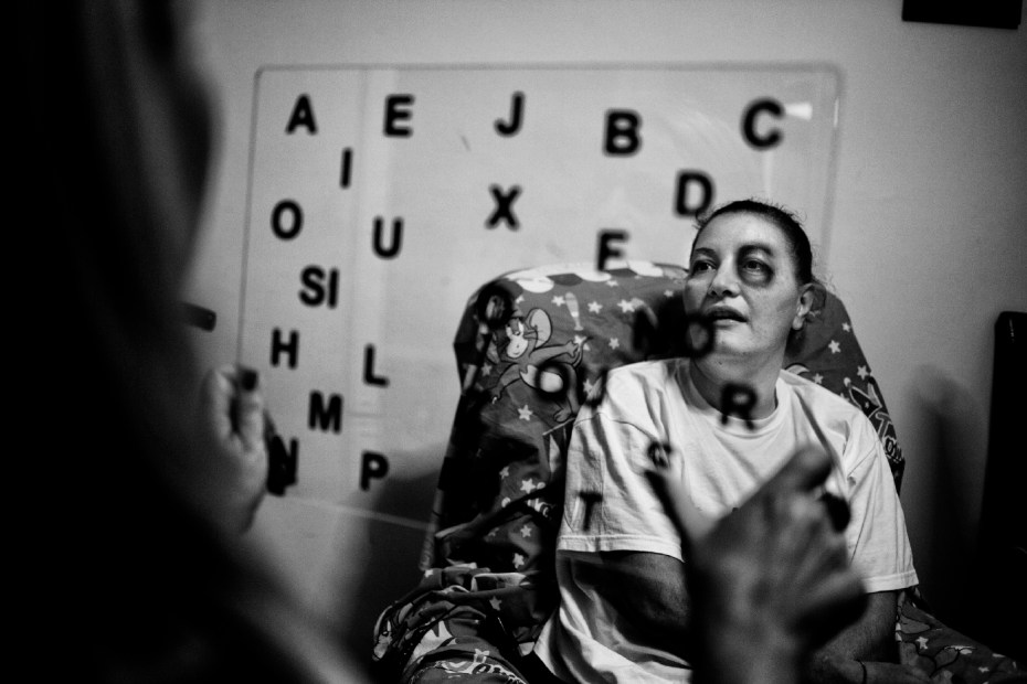 Carla Bocola, 47 years old, affected with lateral amyotrophic sclerosis for the last two years, speaks using eye movement and a table. In Taranto the incidence of SLA (7 to 8 cases every 100.000) is 50% higher than the national average (3 to 4 in every 100.000). Taranto, Italy 2013. © Matteo Bastianelli