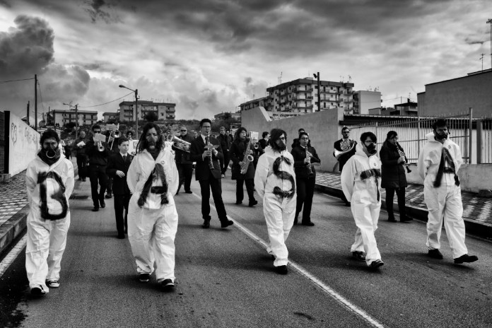 """A crowd of people wearing hazmat suits that say """"STOP"""", are seen protesting against the environmental pollution afflicting the town. Statte (Taranto), Italy 2014. © Matteo Bastianelli"""