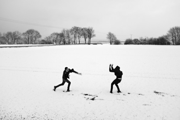 Syrian refugees Hani and Mohamad, both resident in Germany, have a snowball fight in a snow-covered field on the outskirts of town. Anröchte, Germany 2016. © Matteo Bastianelli