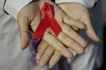 Il fiocco rosso simbolo dell'AIDS tra le mani di una donna