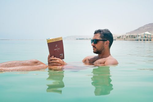 A man sitting in the ocean reading a book.