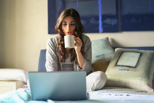 woman sitting on bad in front of laptop with a cup of coffee.