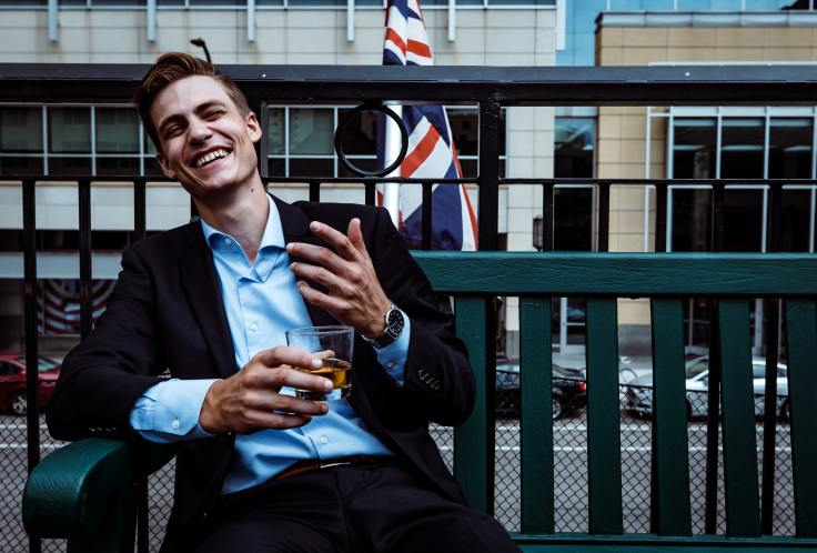 Man laughing on park bench drinking whiskey.