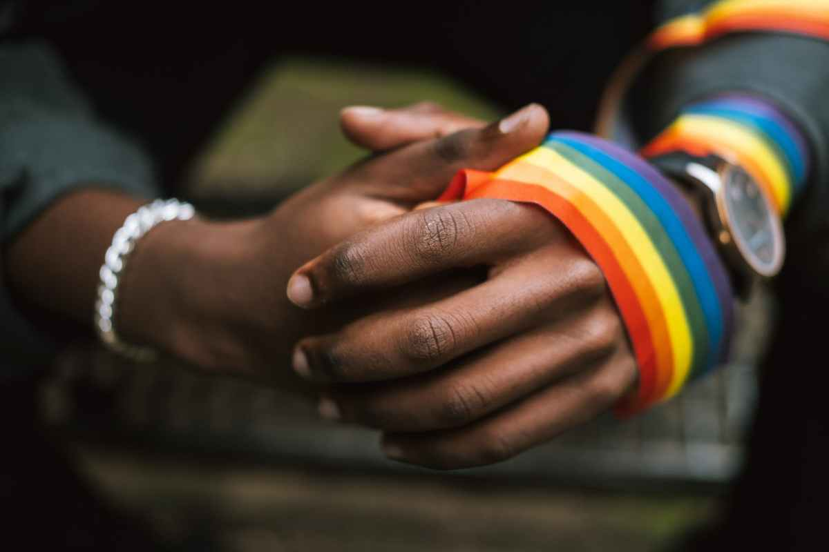 crop unrecognizable black man wearing lgbt ribbon on arm