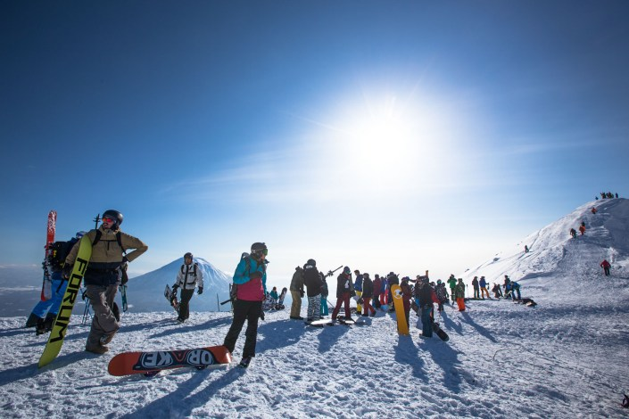 a line of people hike along the peak of niseko with mount yotei in the background