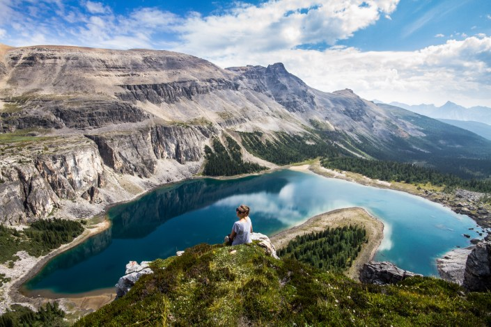 a girl sits on the edge of a cliff overlooking a blue alpine lake in the canadian rocky mountains