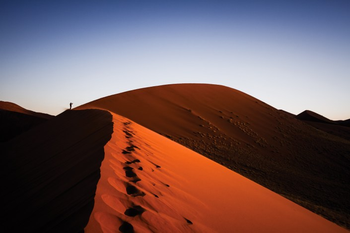 blue skies and red sand of the desert in namibia at sunset