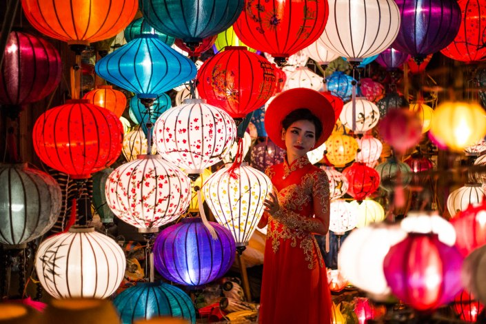 a beautiful woman gets her portrait amongst alot of lanterns on the streets of Hoi An
