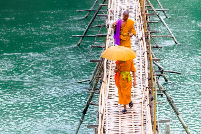 monks crossing a bamboo bridge on the shores of the mekong river