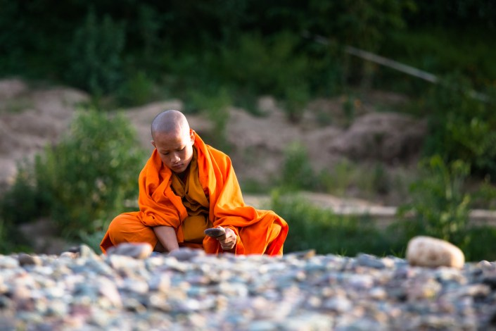 a monk sits on the shore in a vibrant orange playing with stones