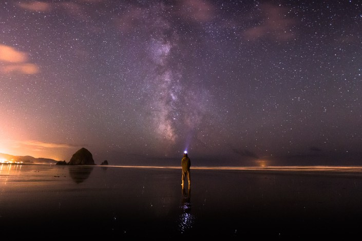 A man stands in the ocean stargazing on the milkyway above in the night sky