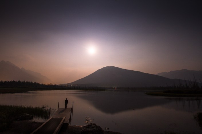 a smokey moonrise over a still alpine lake