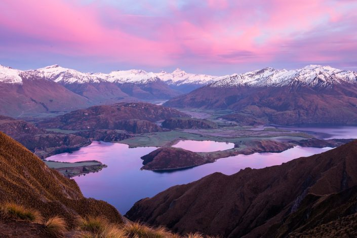 the sun rises over a snowcapped mountain range casting pink clouds and a lake below reflecting the colours