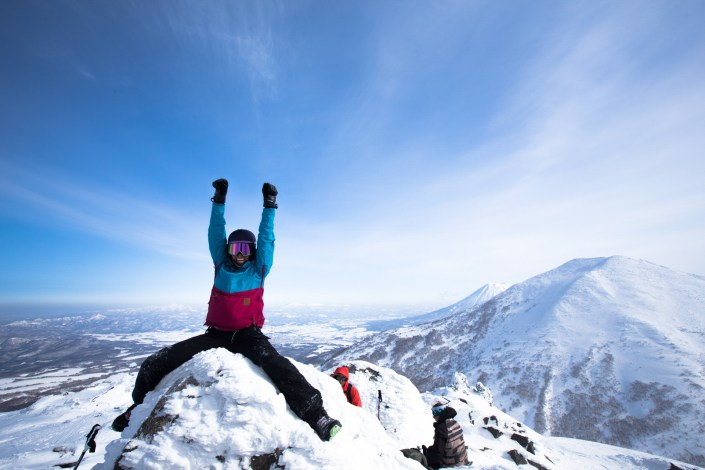 a snowboarder celebrates at the top of a mountain in japans backcountry