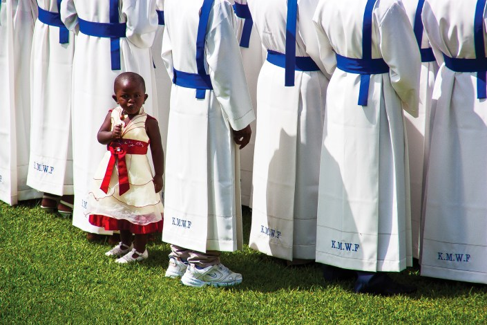 a young Rwandan child looks back while all the adults look forward during a chrictmas ceremony in Kigali