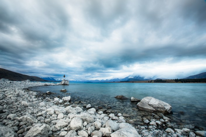 a lone figure stands ona rock under a storm at lake tekapu new zealand
