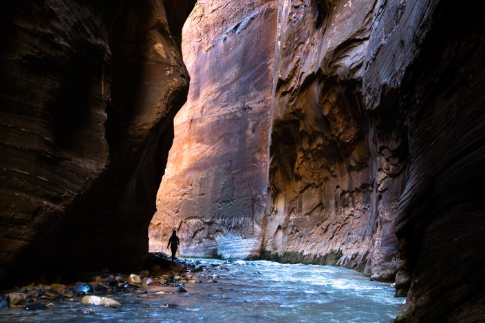 A person walking in the narrows of Zion National Park