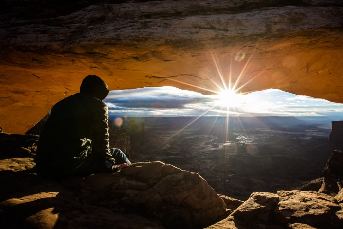 the sun is seen rising under a natural arch in canyon lands national park